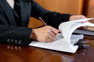 Manos de notario firmando papeles de cancelación hipotecaria