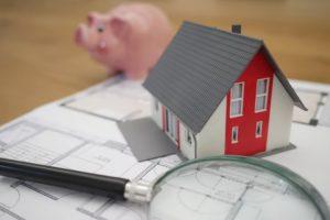 Hucha cerdo, casa y lupa sobre papeles de hipoteca